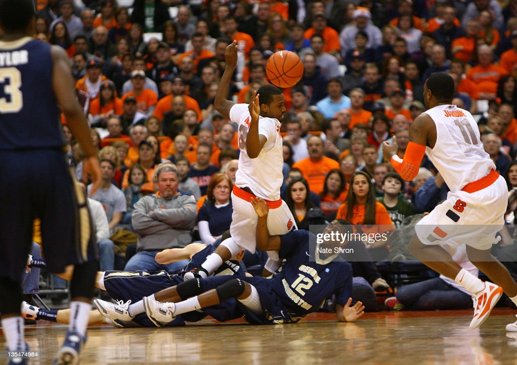 Kris Joseph of the Syracuse Orange loses the ball as he trips over David Pellom of the George Washington Colonials during the game at the Carrier...