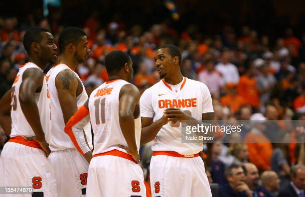 Kris Joseph of the Syracuse Orange talks with teammates Scoop Jardine Fab Melo and Rakeem Christmas during the game against the George Washington...