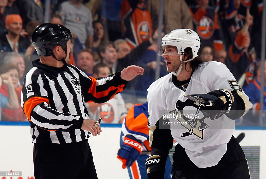 Kris Letang #58 of the Pittsburgh Penguins argues a penalty call with referee Dan O'Halloran #13 during the game against the New York Islanders in Game Four of the Eastern Conference Quarterfinals during the 2013 NHL Stanley Cup Playoffs at the Nassau Veterans Memorial Coliseum on May 7, 2013 in Uniondale, New York.
