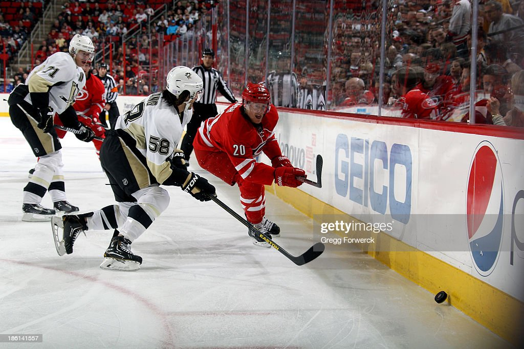 Kris Letang #58 of the Pittsburgh Penguins closes in to defend Riley Nash #20 of the Carolina Hurricanes as he chases the puck along the boards during during an NHL game at PNC Arena on October 28, 2013 in Raleigh, North Carolina.