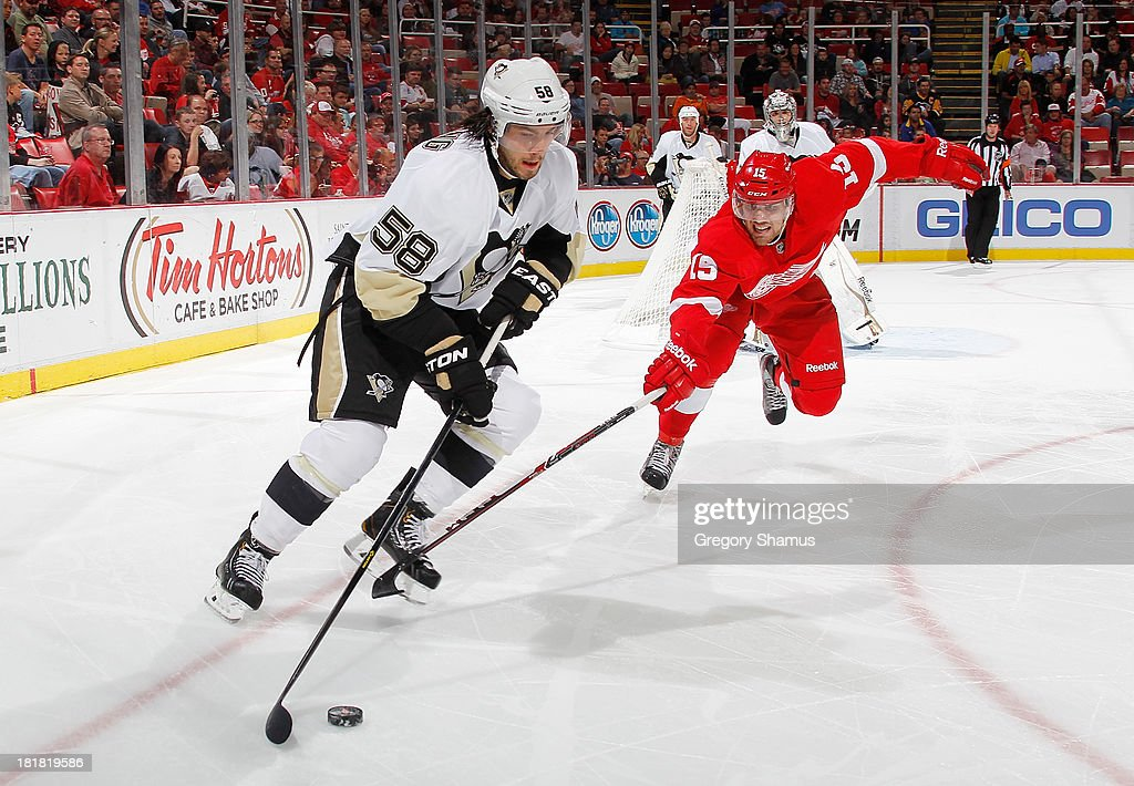<a gi-track='captionPersonalityLinkClicked' href=/galleries/search?phrase=Kris+Letang&family=editorial&specificpeople=3966336 ng-click='$event.stopPropagation()'>Kris Letang</a> #58 of the Pittsburgh Penguins tries to get around the stick of <a gi-track='captionPersonalityLinkClicked' href=/galleries/search?phrase=Riley+Sheahan&family=editorial&specificpeople=7029365 ng-click='$event.stopPropagation()'>Riley Sheahan</a> #15 of the Detroit Red Wings in the second period during a pre season game at Joe Louis Arena on September 25, 2013 in Detroit, Michigan.