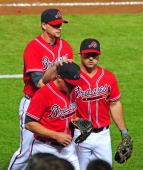 Kris Medlen of the Atlanta Braves is consoled by Dan Uggla and Chris Johnson after losing his nohit bid in the sixth inning against the Philadelphia...