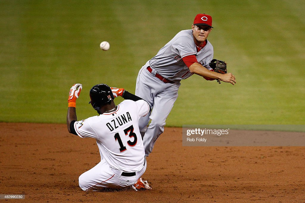 Kris Negron #17 of the Cincinnati Reds turns a double play over <a gi-track='captionPersonalityLinkClicked' href=/galleries/search?phrase=Marcell+Ozuna&family=editorial&specificpeople=10358366 ng-click='$event.stopPropagation()'>Marcell Ozuna</a> #13 of the Miami Marlins during the second inning of the game at Marlins Park on July 31, 2014 in Miami, Florida.