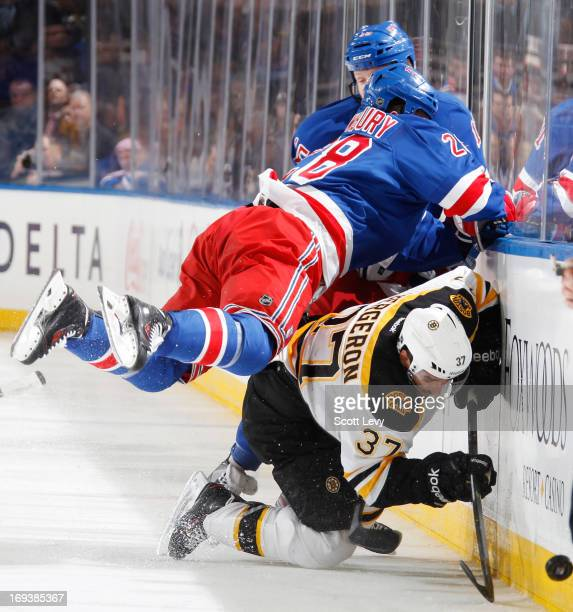 Kris Newbury of the New York Rangers attempts to hit Patrice Bergeron of the Boston Bruins in Game Four of the Eastern Conference Semifinals during...