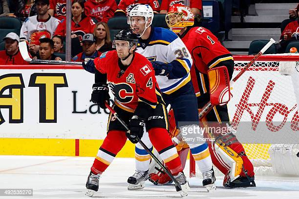 Kris Russell and Jonas Hiller of the Calgary Flames skate against Troy Brouwer of the St Louis Blues during an NHL game at Scotiabank Saddledome on...