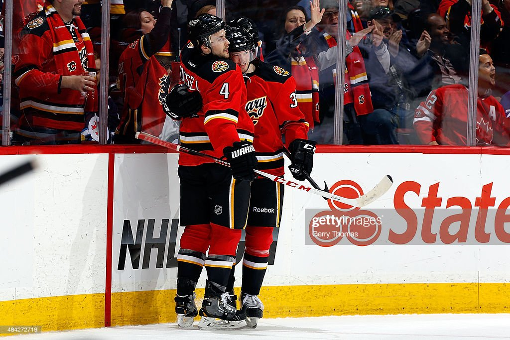 Kris Russell #4 and Paul Byron #32 of the Calgary Flames celebrate a goal against the Winnipeg Jets at Scotiabank Saddledome on April 11, 2014 in Calgary, Alberta, Canada.