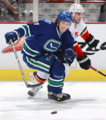 Kris Russell of the Calgary Flames and David Booth of the Vancouver Canucks skate after a loose puck during their NHL game at Rogers Arena April 13...