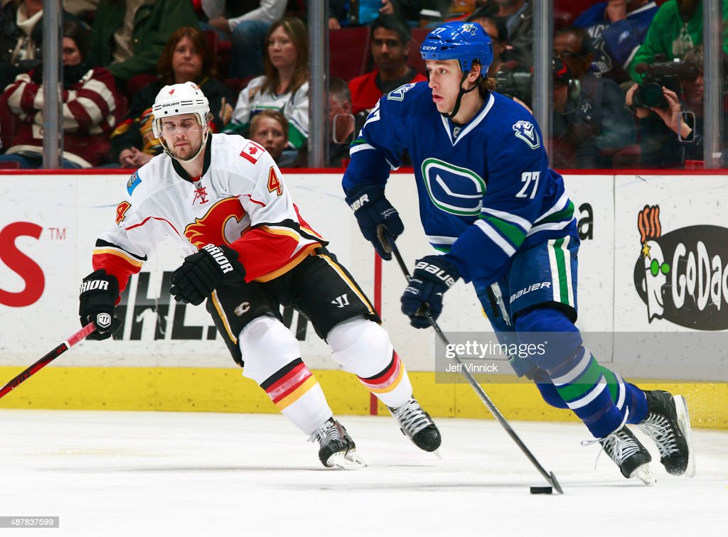 Kris Russell #4 of the Calgary Flames and Shawn Matthias #27 of the Vancouver Canucks skate up ice during their NHL game at Rogers Arena April 13, 2014 in Vancouver, British Columbia, Canada. Vancouver won 5-1.