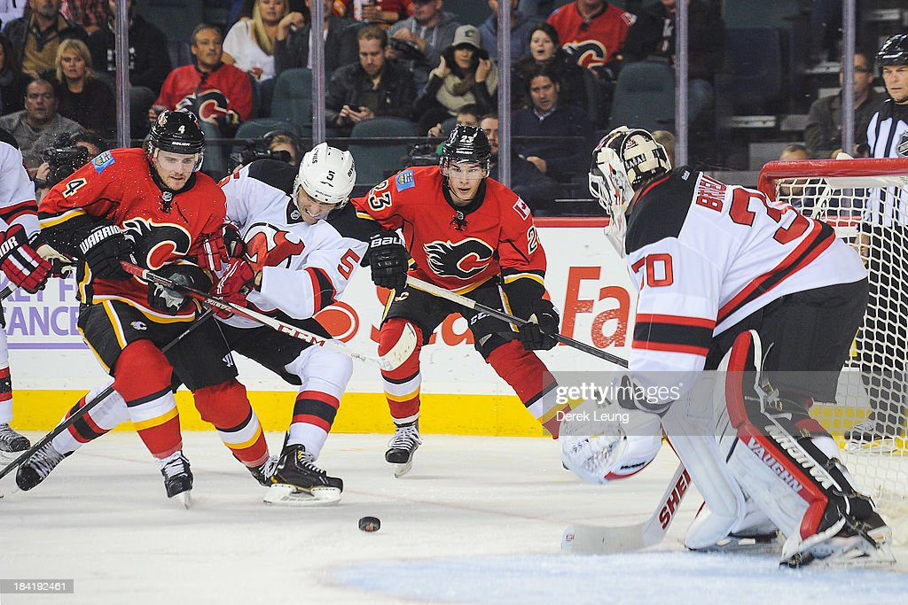 <a gi-track='captionPersonalityLinkClicked' href=/galleries/search?phrase=Kris+Russell&family=editorial&specificpeople=879805 ng-click='$event.stopPropagation()'>Kris Russell</a> #4 of the Calgary Flames battles for the puck against <a gi-track='captionPersonalityLinkClicked' href=/galleries/search?phrase=Adam+Larsson&family=editorial&specificpeople=6705080 ng-click='$event.stopPropagation()'>Adam Larsson</a> #5 of the New Jersey Devils while in front of the net of <a gi-track='captionPersonalityLinkClicked' href=/galleries/search?phrase=Martin+Brodeur&family=editorial&specificpeople=201594 ng-click='$event.stopPropagation()'>Martin Brodeur</a> #30 of the Devils during an NHL game at Scotiabank Saddledome on October 11, 2013 in Calgary, Alberta, Canada. The Calgary Flames defeated the New Jersey Devils 3-2.