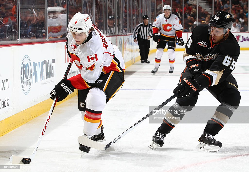 <a gi-track='captionPersonalityLinkClicked' href=/galleries/search?phrase=Kris+Russell&family=editorial&specificpeople=879805 ng-click='$event.stopPropagation()'>Kris Russell</a> #4 of the Calgary Flames battles for the puck against <a gi-track='captionPersonalityLinkClicked' href=/galleries/search?phrase=Emerson+Etem&family=editorial&specificpeople=6365314 ng-click='$event.stopPropagation()'>Emerson Etem</a> #65 of the Anaheim Ducks on October 16, 2013 at Honda Center in Anaheim, California.
