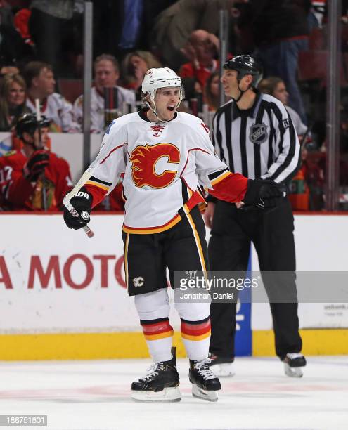 Kris Russell of the Calgary Flames celebrates his gamewinning overtime goal against the Chicago Blackhawks at the United Center on November 3 2013 in...