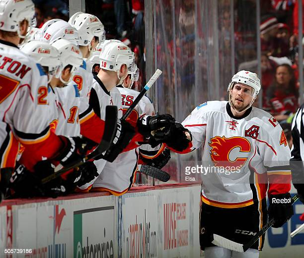 Kris Russell of the Calgary Flames celebrates his goal with teammates on the bench in the second period against the New Jersey Devils on January...