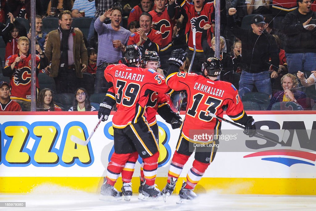 Kris Russell #4 (C) of the Calgary Flames celebrates scoring the team's first goal against the Washington Capitals along with teammates T.J. Galiardi #39 and Mike Cammalleri #13 during an NHL game at Scotiabank Saddledome on October 26, 2013 in Calgary, Alberta, Canada.