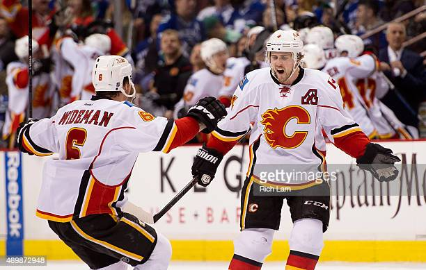 Kris Russell of the Calgary Flames celebrates with Dennis Wideman after scoring what proved to be the game winning goal against the Vancouver Canucks...