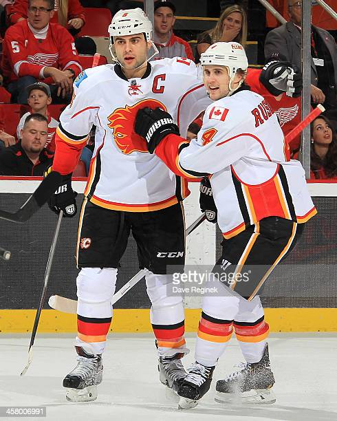 Kris Russell of the Calgary Flames congratulates teammate Mark Giordano after scoring a powerplay goal during an NHL game against the Detroit Red...