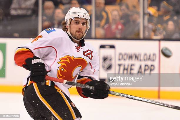 Kris Russell of the Calgary Flames dumps the puck down the ice against the Boston Bruins at the TD Garden on March 5 2015 in Boston Massachusetts