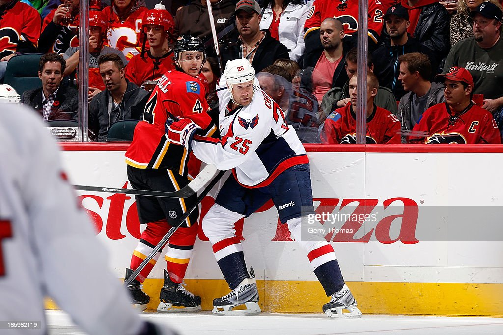 <a gi-track='captionPersonalityLinkClicked' href=/galleries/search?phrase=Kris+Russell&family=editorial&specificpeople=879805 ng-click='$event.stopPropagation()'>Kris Russell</a> #4 of the Calgary Flames skates against <a gi-track='captionPersonalityLinkClicked' href=/galleries/search?phrase=Jason+Chimera&family=editorial&specificpeople=211264 ng-click='$event.stopPropagation()'>Jason Chimera</a> #25 of the Washington Capitals at Scotiabank Saddledome on October 26, 2013 in Calgary, Alberta, Canada.