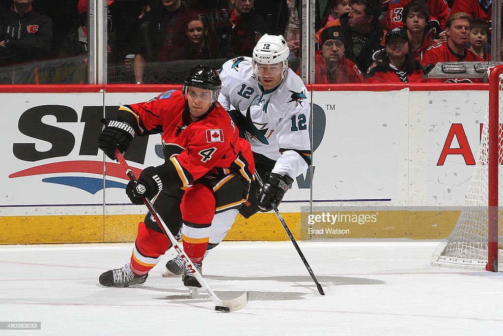 Kris Russell #4 of the Calgary Flames skates against Patrick Marleau #12 of the San Jose Sharks at Scotiabank Saddledome on March 24, 2014 in Calgary, Alberta, Canada.