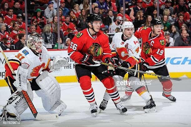 Kris Russell of the Calgary Flames waits in position in between Marko Dano and Jonathan Toews of the Chicago Blackhawks next to goalie Karri Ramo in...