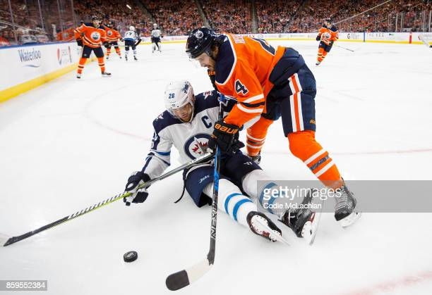 Kris Russell of the Edmonton Oilers battles against Blake Wheeler of the Winnipeg Jets at Rogers Place on October 9 2017 in Edmonton Canada