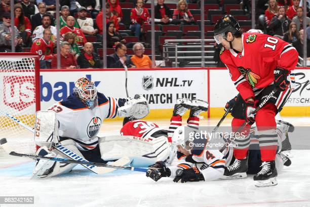 Kris Russell of the Edmonton Oilers falls in between goalie Cam Talbot and Patrick Sharp of the Chicago Blackhawks in the second period at the United...