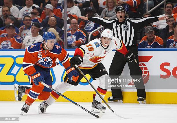 Kris Russell of the Edmonton Oilers skates against Matthew Tkachuk of the Calgary Flames on October 12 2016 at Rogers Place in Edmonton Alberta Canada