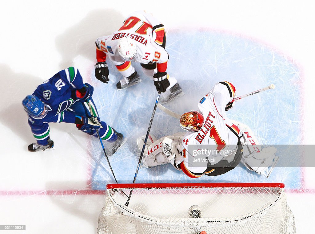 Kris Versteeg #10 of the Calgary Flames and Brandon Sutter #20 of the Vancouver Canucks watch as a shot from teammate Loui Eriksson #21 passes goaltender Brian Elliott #1 of the Calgary Flames during their NHL game at Rogers Arena January 6, 2017 in Vancouver, British Columbia, Canada. Vancouver won 4-2.