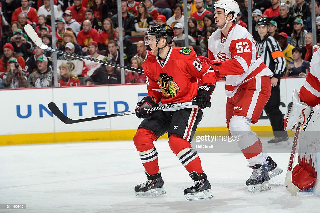 Kris Versteeg of the Chicago Blackhawks and Jonathan Ericsson of the Detroit Red Wings stand in position during the NHL game on March 16 2014 at the...