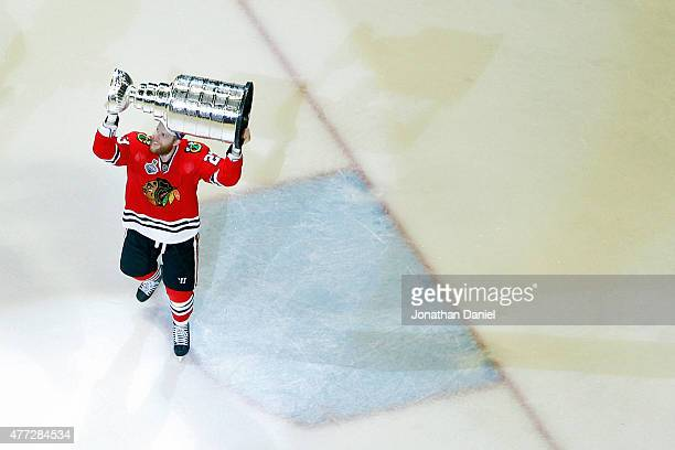 Kris Versteeg of the Chicago Blackhawks celebrates by hoisting the Stanley Cup after defeating the Tampa Bay Lightning by a score of 20 in Game Six...