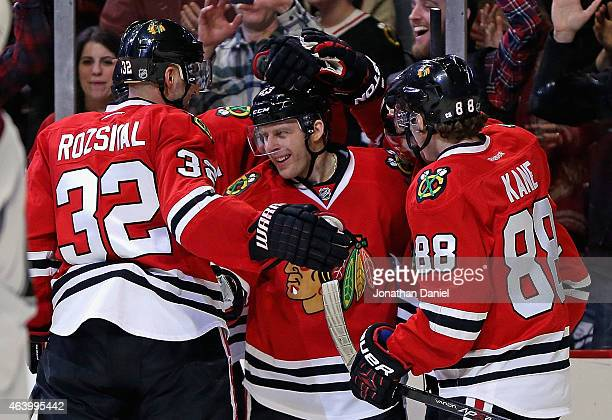 Kris Versteeg of the Chicago Blackhawks celebrates his second period goal with Michal Rozsival and Patrick Kane against the Colorado Avalanche at the...