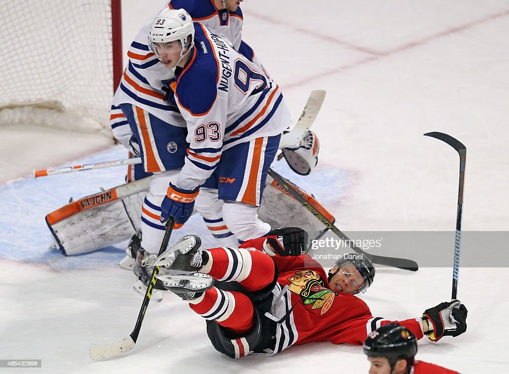 Kris Versteeg #23 of the Chicago Blackhawks hits the ice next to Ryan Nugent-Hopkins #93 of the Edmonton Oilers at the United Center on March 6, 2015 in Chicago, Illinois.