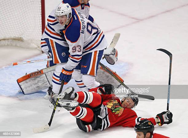 Kris Versteeg of the Chicago Blackhawks hits the ice next to Ryan NugentHopkins of the Edmonton Oilers at the United Center on March 6 2015 in...