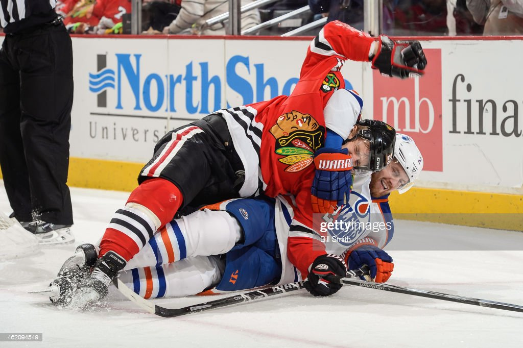 Kris Versteeg of the Chicago Blackhawks is pulled down by Jeff Petry of the Edmonton Oilers during the NHL game on January 12 2014 at the United...
