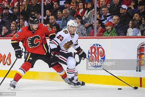 Kris Versteeg of the Chicago Blackhawks skates with the puck against Chris Butler of the Calgary Flames during an NHL game at Scotiabank Saddledome...