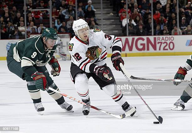 Kris Versteeg of the Chicago Blackhawks takes control of the puck as Mikko Koivu of the Minnesota Wild reaches from behind on October 26 2009 at the...