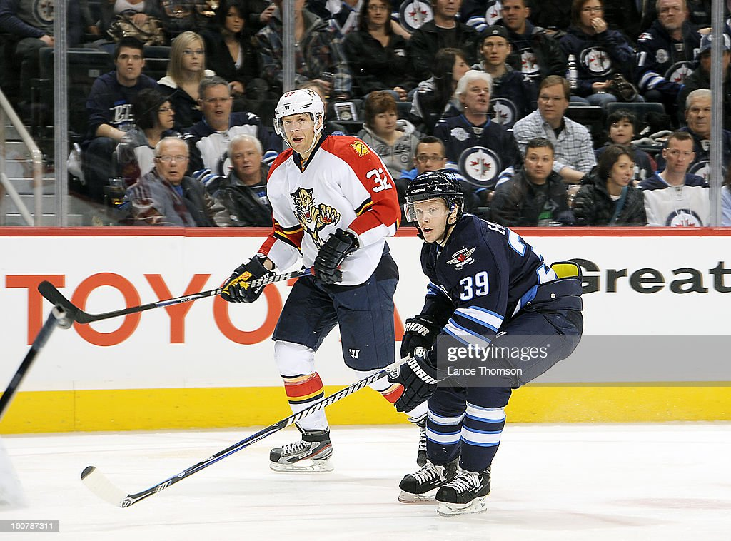 <a gi-track='captionPersonalityLinkClicked' href=/galleries/search?phrase=Kris+Versteeg&family=editorial&specificpeople=2242969 ng-click='$event.stopPropagation()'>Kris Versteeg</a> #32 of the Florida Panthers and <a gi-track='captionPersonalityLinkClicked' href=/galleries/search?phrase=Tobias+Enstrom&family=editorial&specificpeople=2538468 ng-click='$event.stopPropagation()'>Tobias Enstrom</a> #39 of the Winnipeg Jets follow the play down the ice during third period action at the MTS Centre on February 5, 2013 in Winnipeg, Manitoba, Canada.