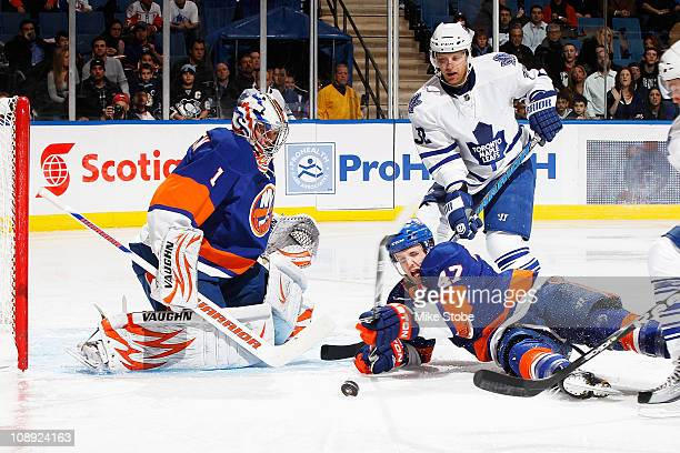 Kris Versteeg of the Toronto Maple Leafs takes a shot as Goaltender Mikko Koskinen of the New York Islanders watches as teammate Andrew MacDonald...