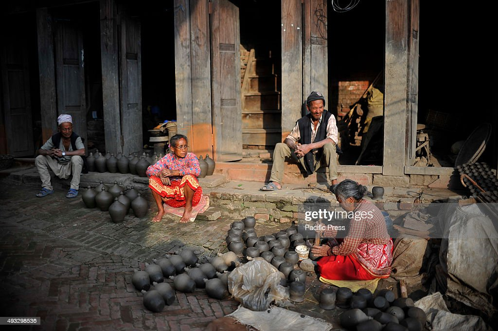 BHAKTAPUR NEPAL KATHMANDU NP NEPAL Krishna Laxmi 65yrs giving final touch up to mud pots before drying it to sun at Pottery Square Bhaktapur is an...