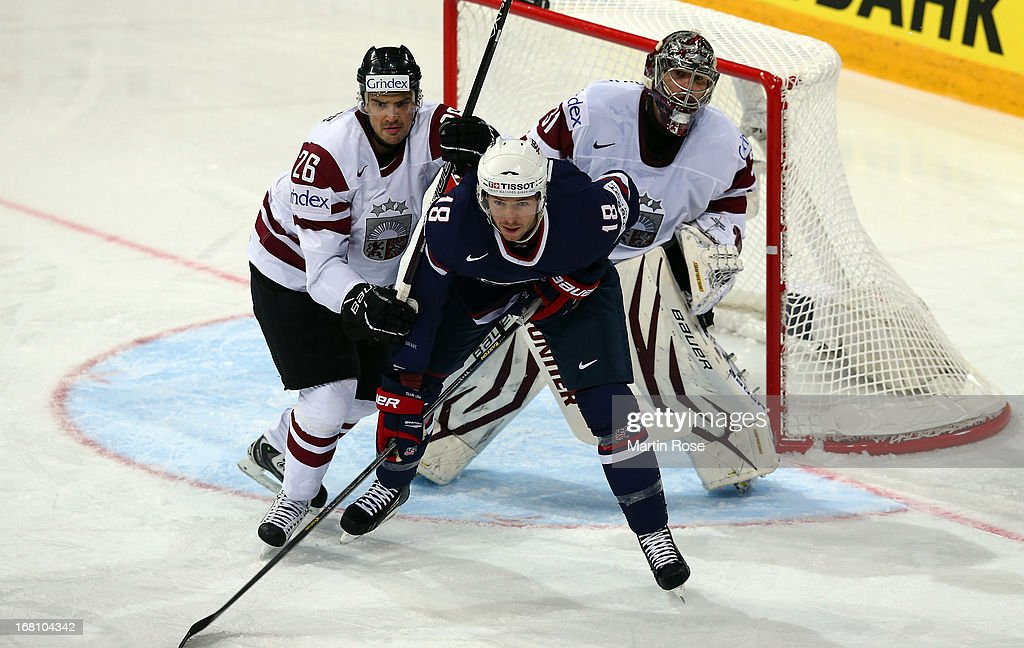 Krisjanis Redlihs (L) of Latvia and David Moss (R) of USA battle for position in front of the net during the IIHF World Championship group H match between Latvia and USA at Hartwall Areena on May 5, 2013 in Helsinki, Finland.