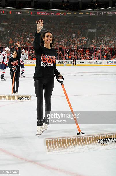 Krista Allysse Cipollone of the Philadelphia Flyers ice girls waves to the crowd as she cleans the ice during a timeout against the Washington...