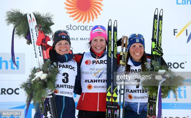 Krista Parmakoski of Finland Marit Bjoergen of Norway and Charlotte Kalla of Sweden pose during during the flower ceromeny after the Women's Cross...