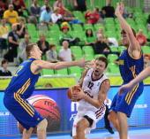 Kristaps Janicenoks of Latvia vies with Maxym Korniyenko and Viacheslav Kravtsov of Ukraine during the FIBA EuroBasket second round Group E...