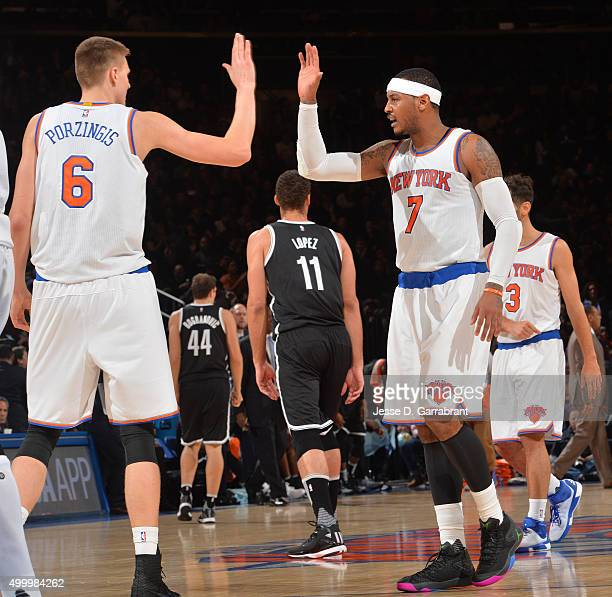 Kristaps Porzingis and Carmelo Anthony of the New York Knicks give each other highfives against the Brooklyn Nets at Madison Square Garden on...