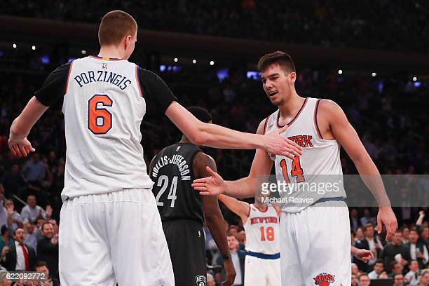 Kristaps Porzingis and Willy Hernangomez of the New York Knicks react against the Brooklyn Nets during the second half at Madison Square Garden on...