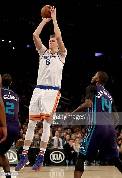 Kristaps Porzingis of the New York Knicks takes a shot as Marvin Williams and Michael KiddGilchrist of the Charlotte Hornets defend at Madison Square...