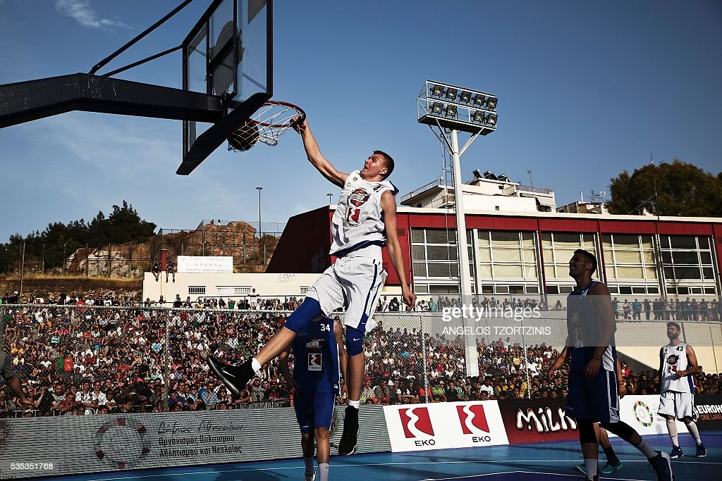 Kristaps Porzingis star of New York Knicks jumps to score during a game of streetball in Athens on May 29, 2016. The Antetokounbros Streetball Event organized by Eurohoops and the City of Athens, took place in an open court and was watched by 5,000 people. / AFP / ANGELOS