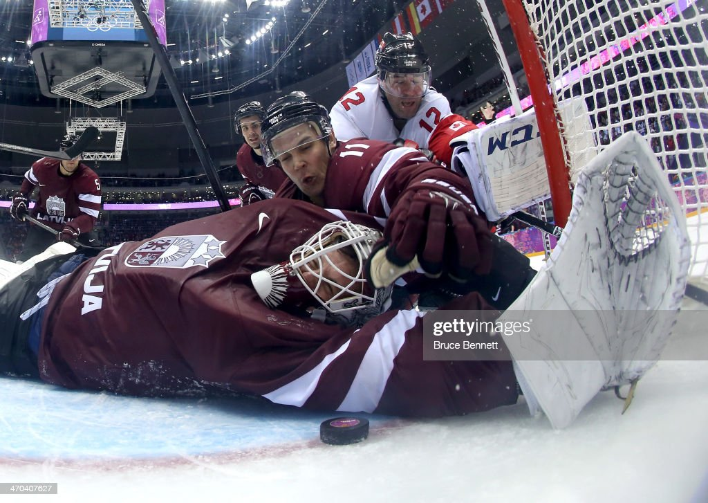 Kristers Gudlevskis #50 of Latvia makes a save against Canada during the third period with the help of teammate <a gi-track='captionPersonalityLinkClicked' href=/galleries/search?phrase=Kristaps+Sotnieks&family=editorial&specificpeople=5699381 ng-click='$event.stopPropagation()'>Kristaps Sotnieks</a> #11 during the Men's Ice Hockey Quarterfinal Playoff on Day 12 of the 2014 Sochi Winter Olympics at Bolshoy Ice Dome on February 19, 2014 in Sochi, Russia.
