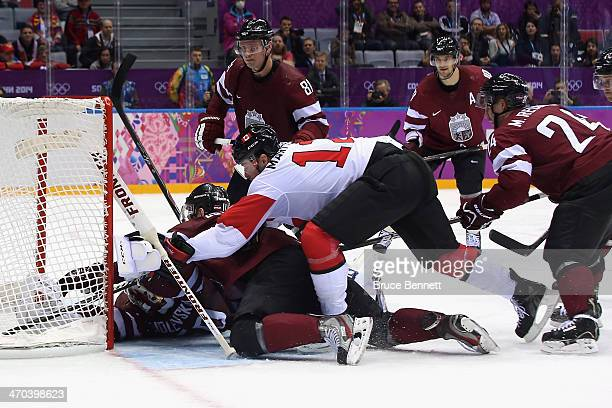 Kristers Gudlevskis of Latvia makes a save as Canadian and Latvian players pile up during the Men's Ice Hockey Quarterfinal Playoff on Day 12 of the...