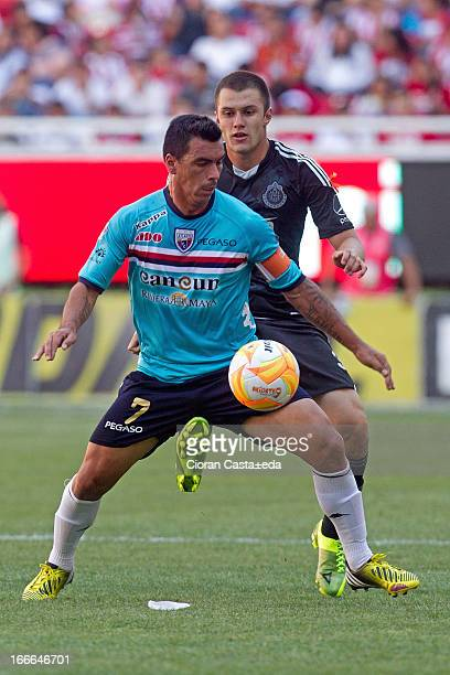 Kristian Alvalez of Chivas competes for the ball with Esteban Paredes of Atlante during a match between Chivas and Atlante as part of the Torneo...