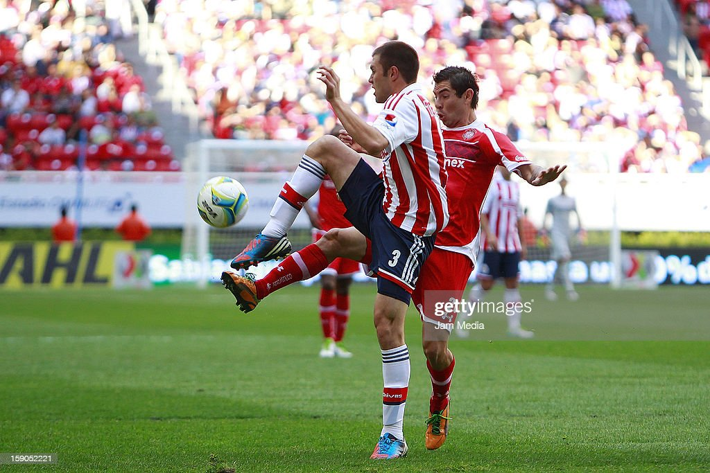 <a gi-track='captionPersonalityLinkClicked' href=/galleries/search?phrase=Kristian+Alvarez&family=editorial&specificpeople=5829726 ng-click='$event.stopPropagation()'>Kristian Alvarez</a> (L) of Chivas struggles for the ball with Flavio Santos (R) of Toluca during the match between Chivas and Toluca as part of the Clausura 2013 Liga MX tournament at Omnilife Stadium on January 06, 2013 in Guadalajara, Mexico.